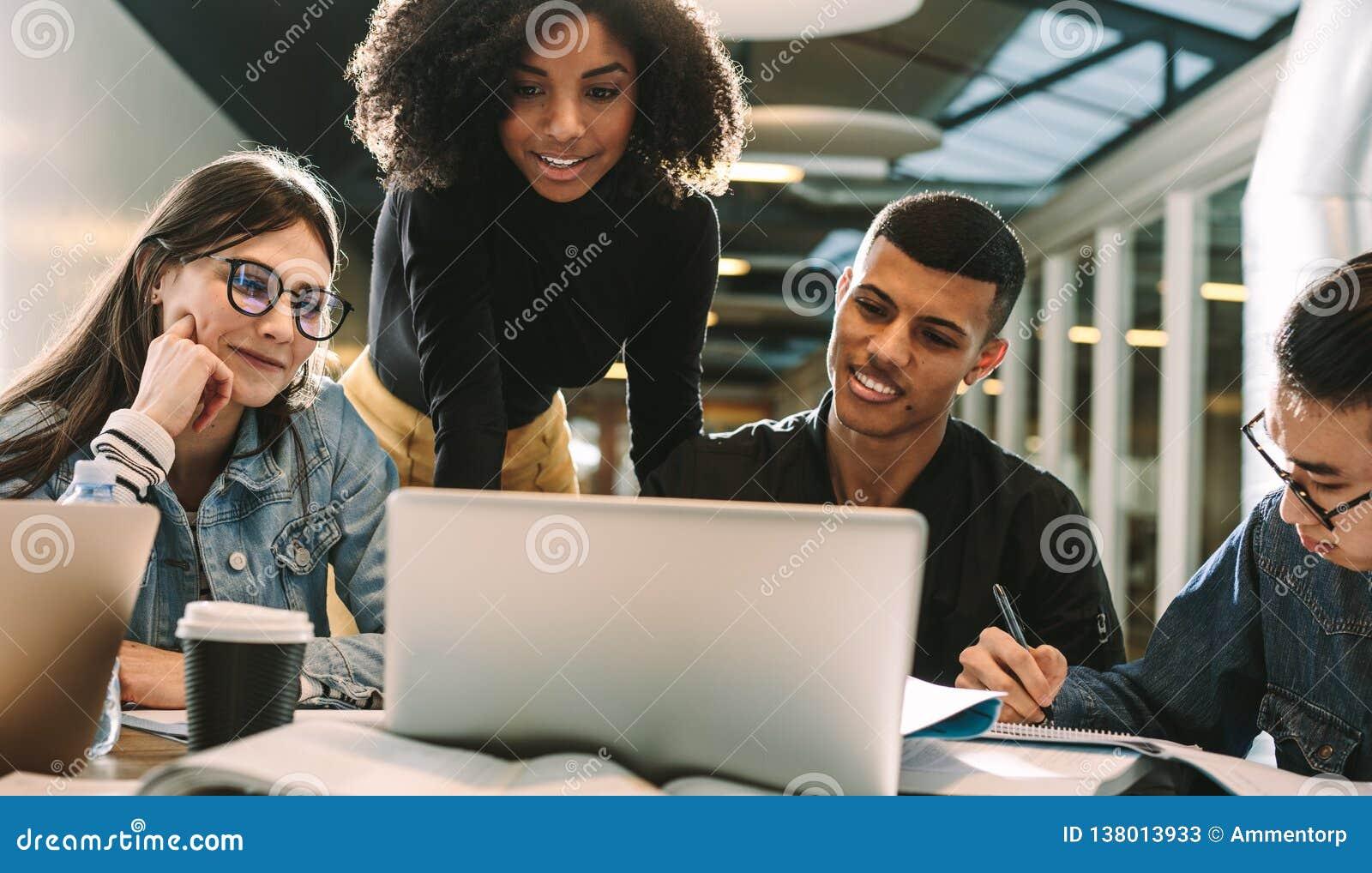 Quatro estudantes que usam o portátil para a pesquisa na biblioteca