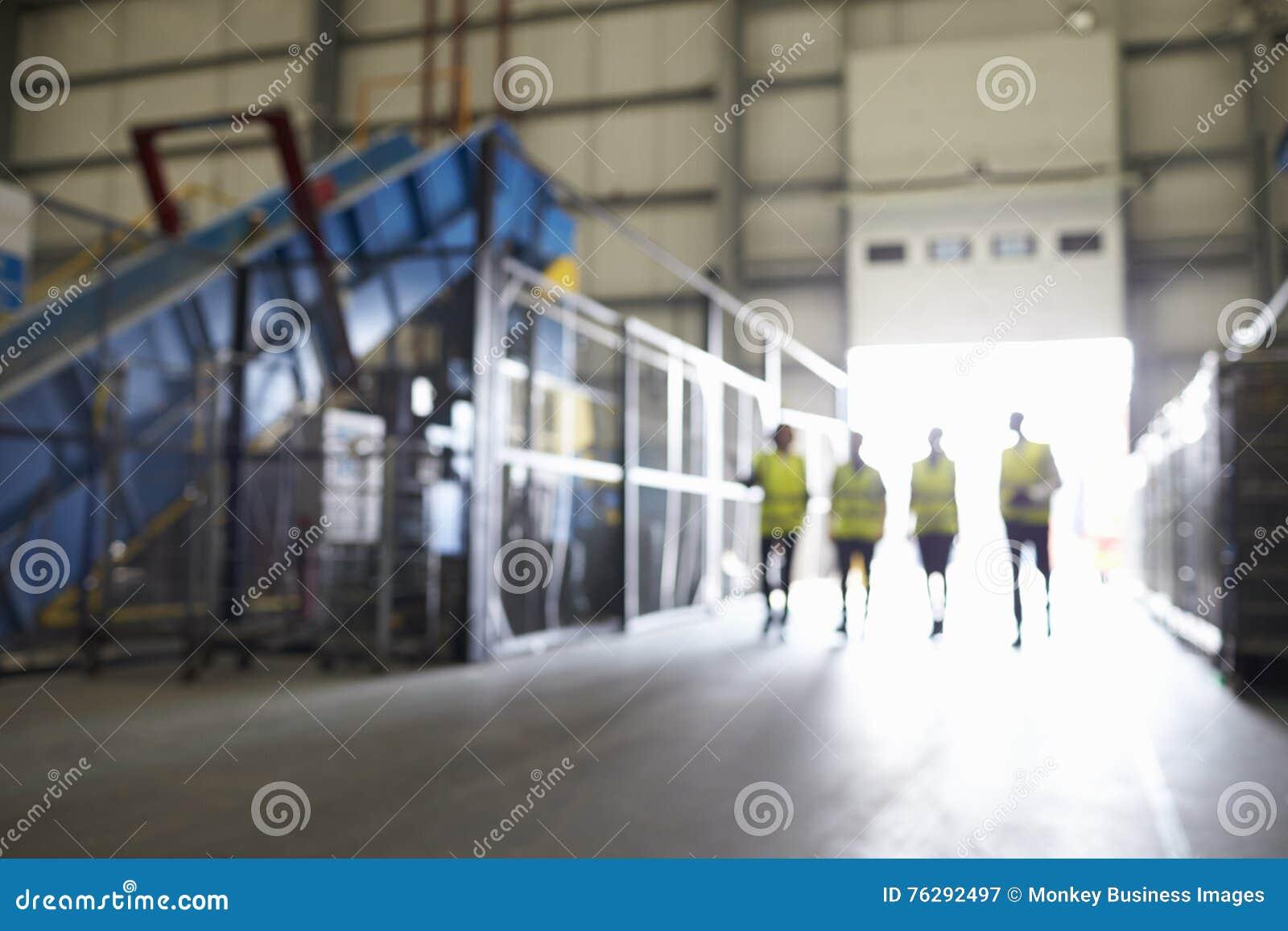 Quatro figuras que andam em um foco interior, macio industrial