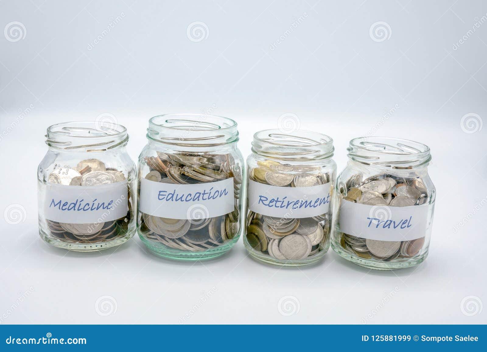 Quatro garrafas de vidro encheram-se com as moedas com papel de etiqueta da medicina, educação, aposentadoria, curso