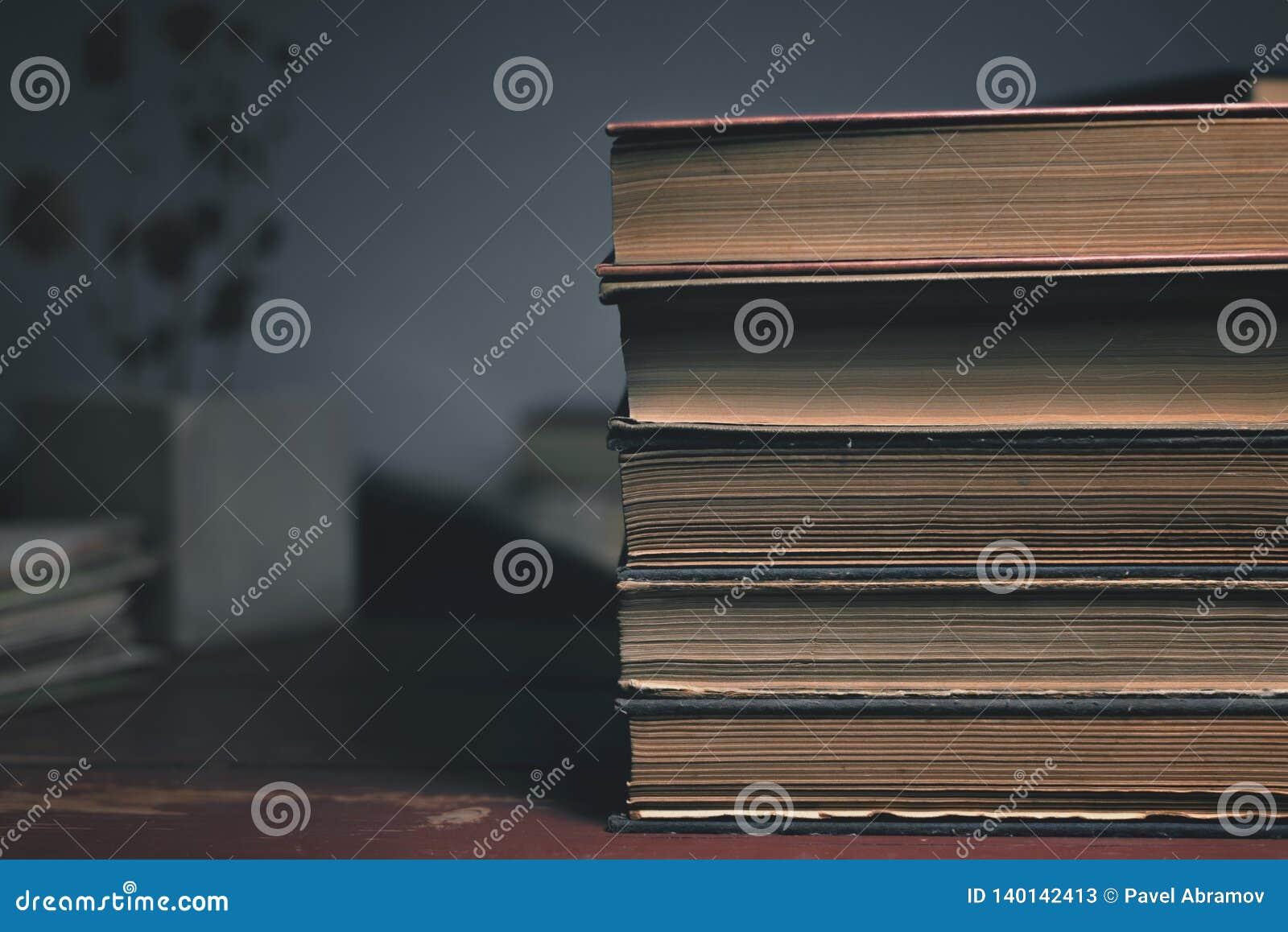 Quatro livros velhos do vintage em uma tabela de madeira e em uma flor seca no fundo