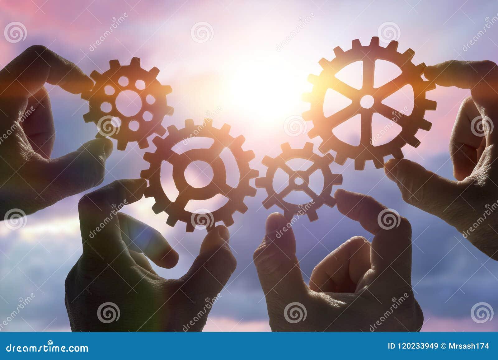 Quatro mãos recolhem um enigma das engrenagens, na perspectiva do céu no por do sol