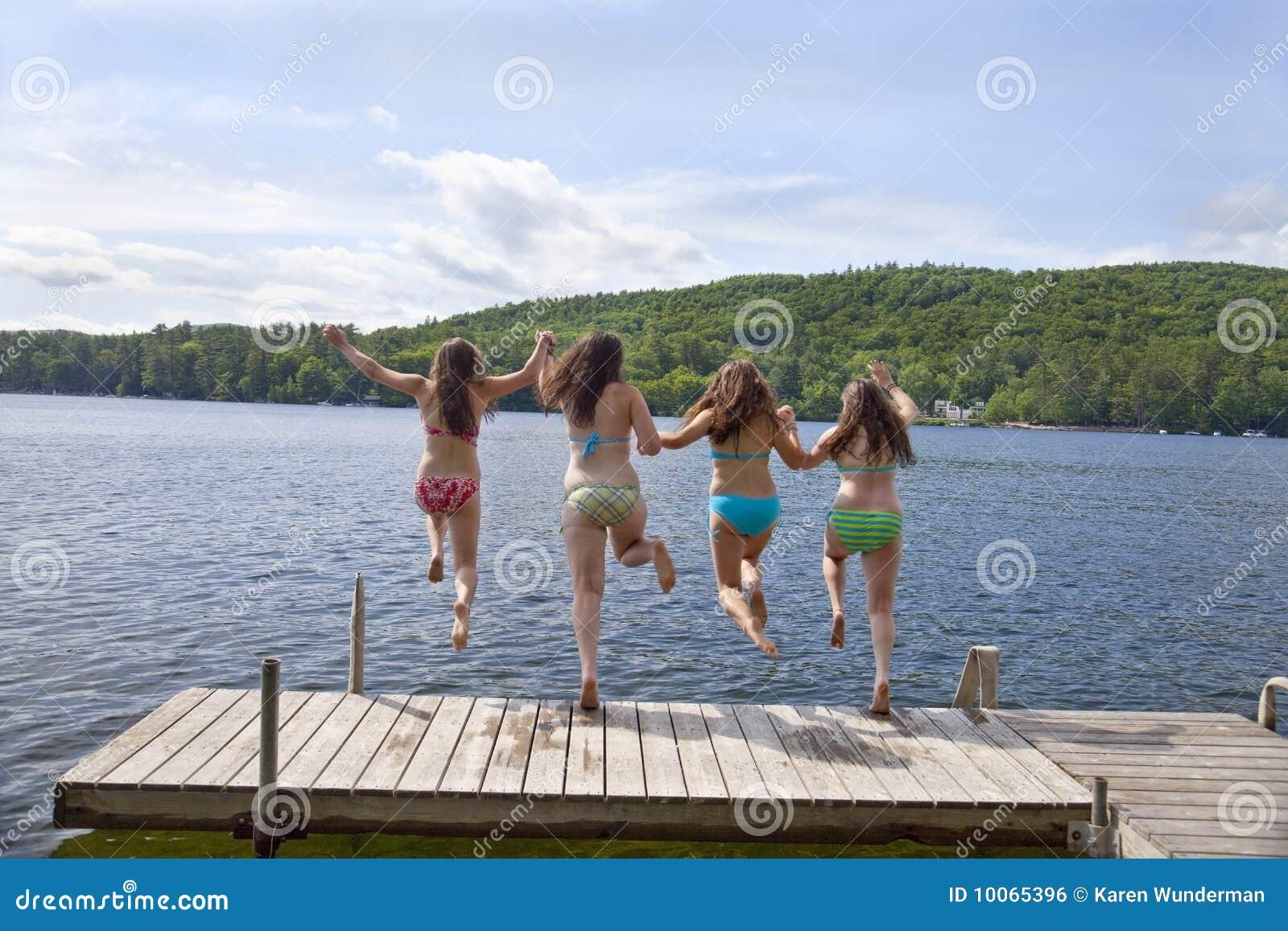 Quatro meninas que saltam fora da doca