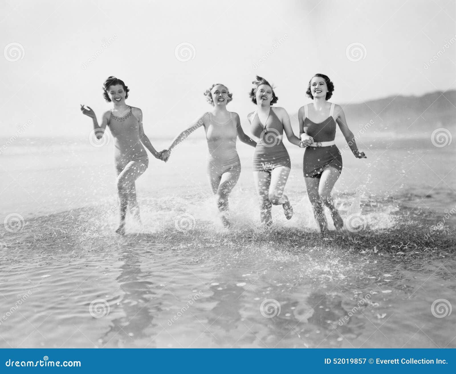 Quatro mulheres que correm na água na praia (todas as pessoas descritas não são umas vivas mais longo e nenhuma propriedade exist