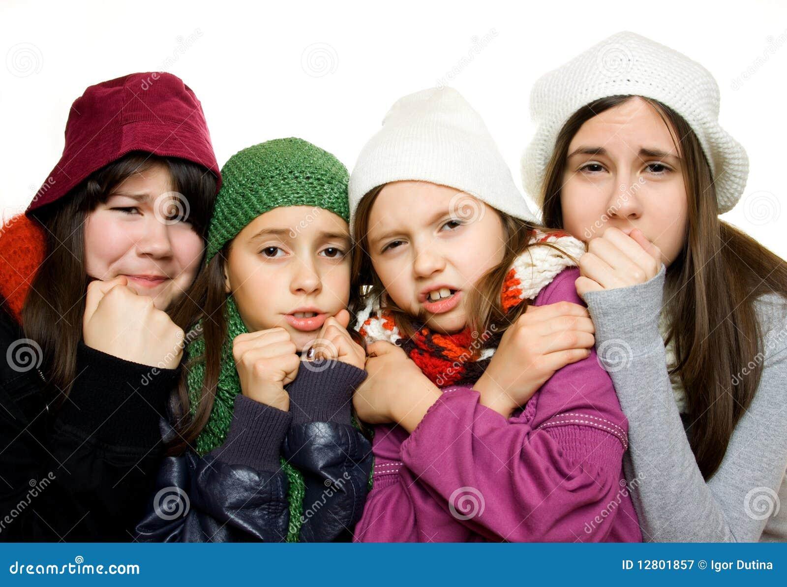 Quatro raparigas no equipamento do inverno