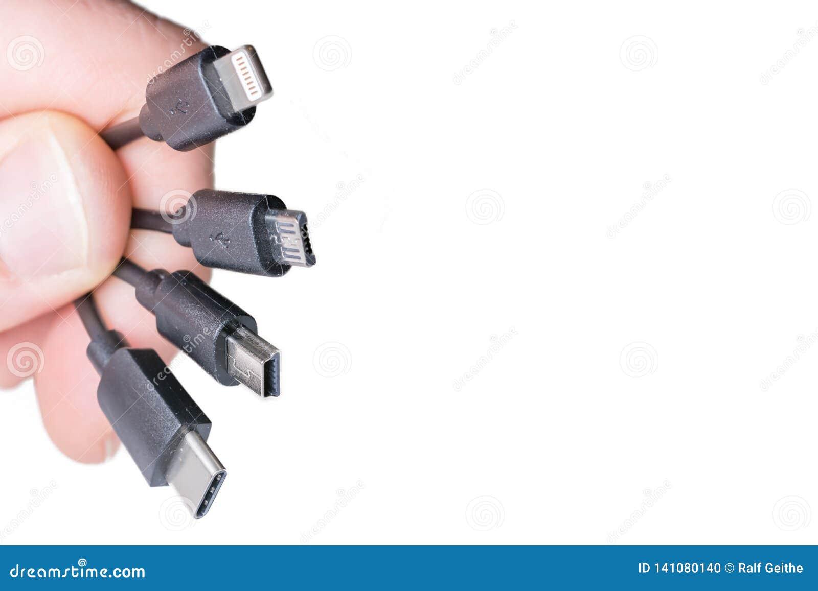 Quatro tipos de cabos de carregamento na frente do fundo branco com espaço da cópia