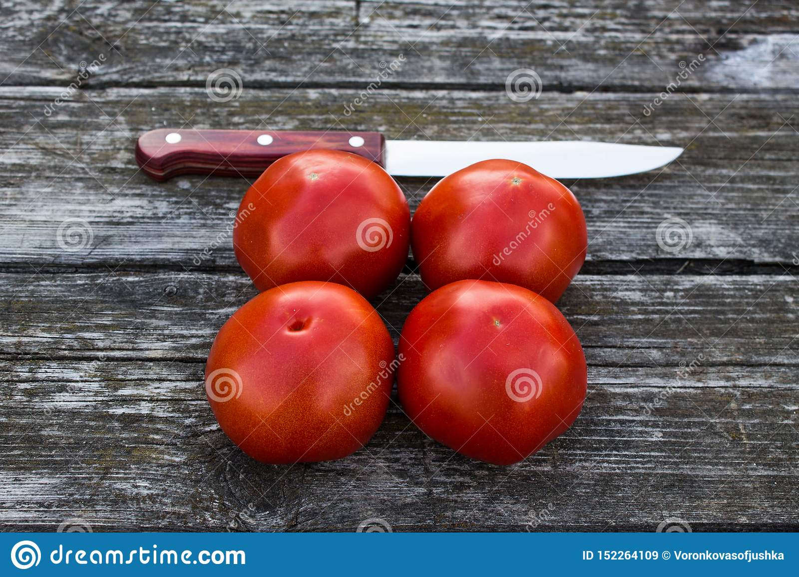 Quatro tomates vermelhos maduros em uma tabela de madeira velha