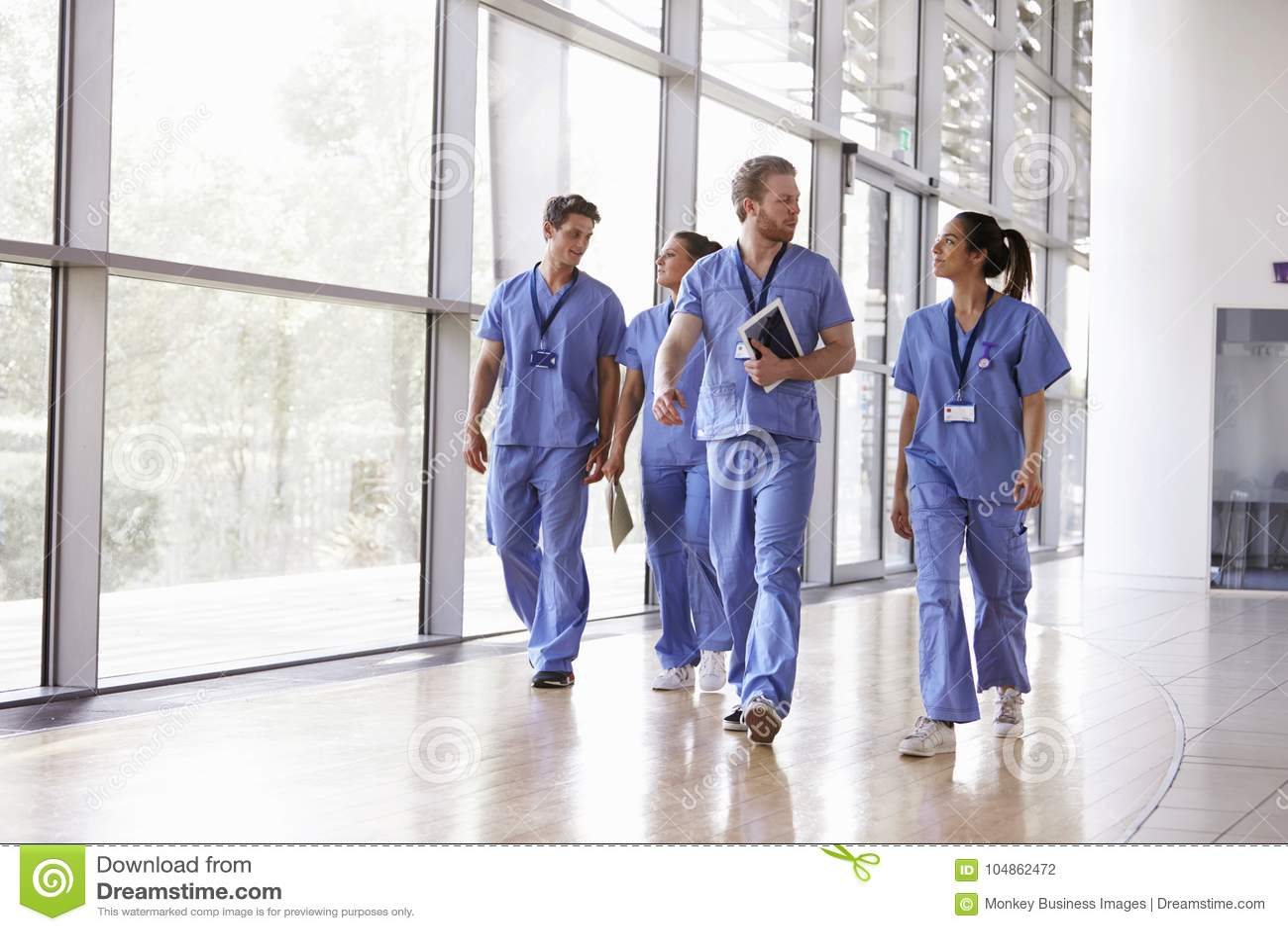 Quatro trabalhadores dos cuidados médicos esfregam dentro o passeio no corredor