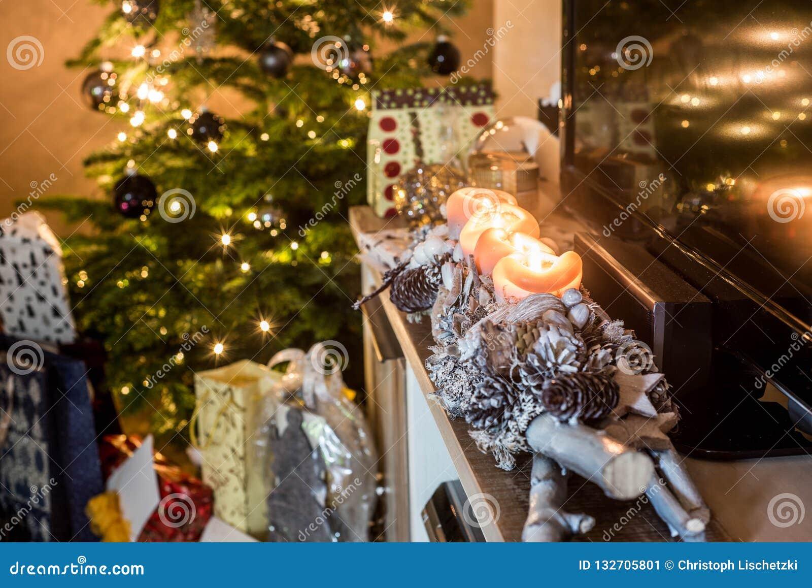 Quatro velas de queimadura do advento, luzes decoradas bonitas da instalação na árvore de Natal do fundo com presentes