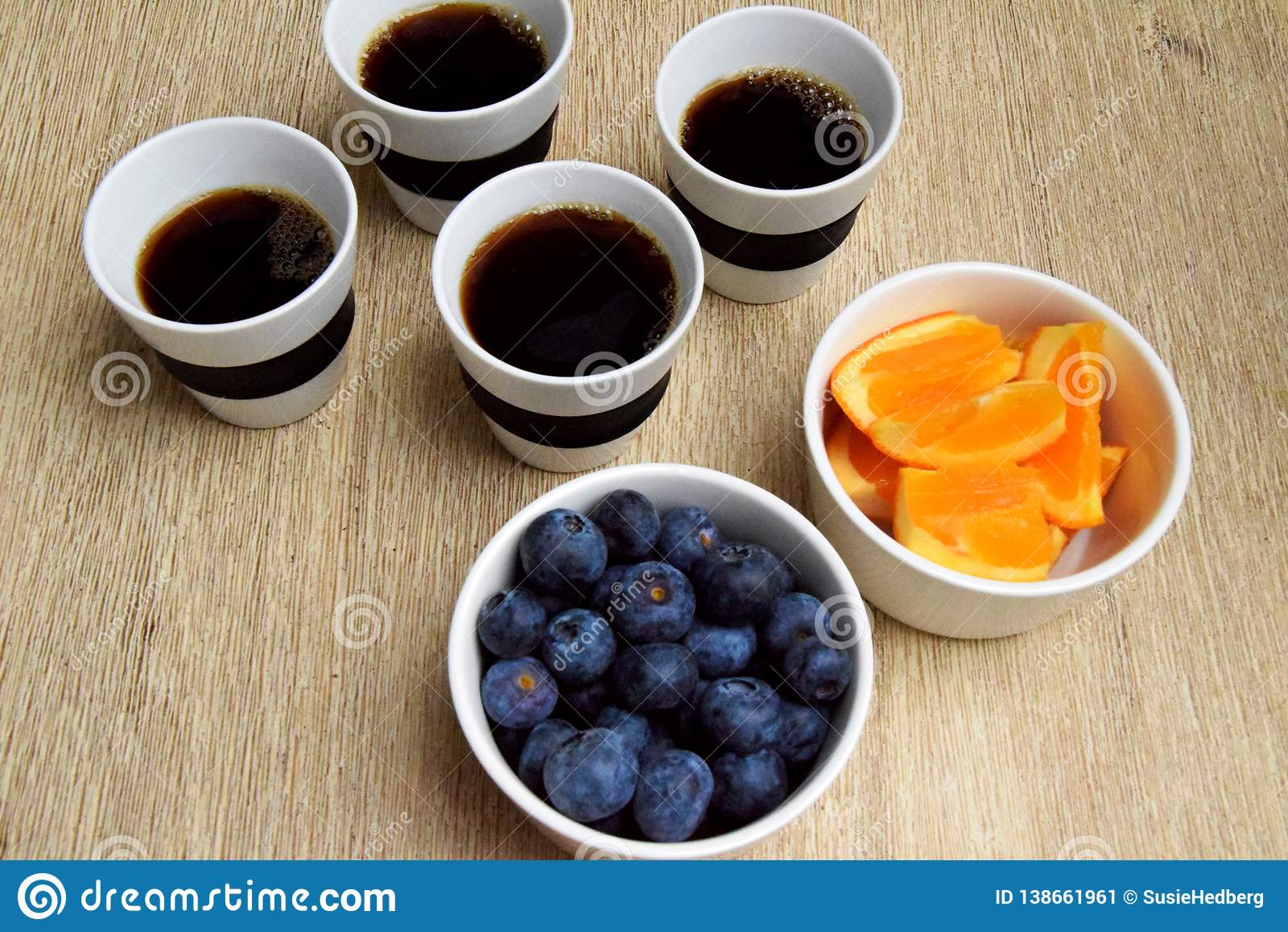 Quatro xícaras de café e petisco saudável do fruto