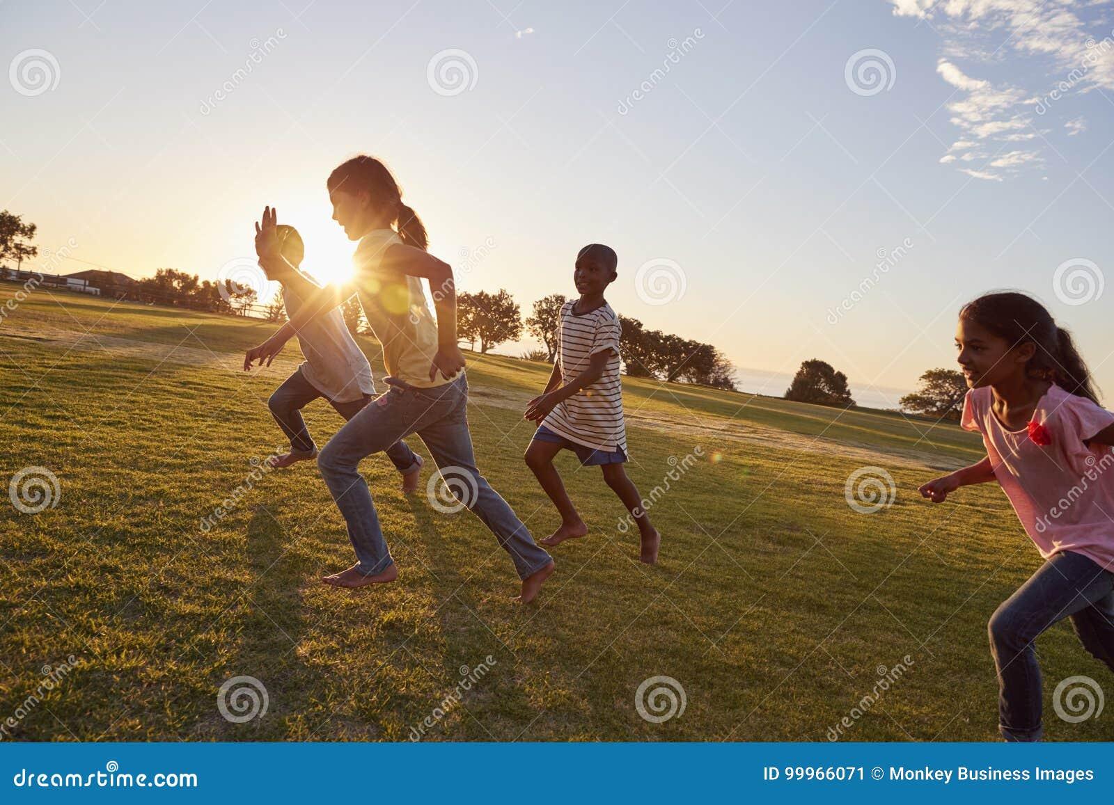 Quattro bambini che corrono a piedi nudi in salita in un parco