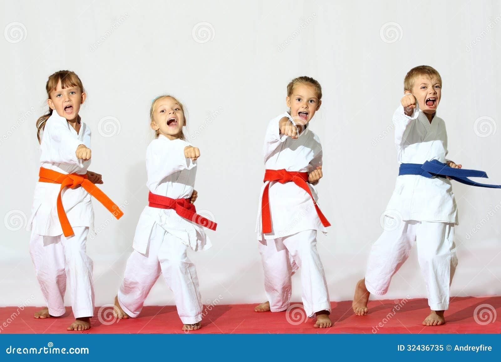 Quattro bambini in kimono hanno colpito una perforazione su un fondo bianco