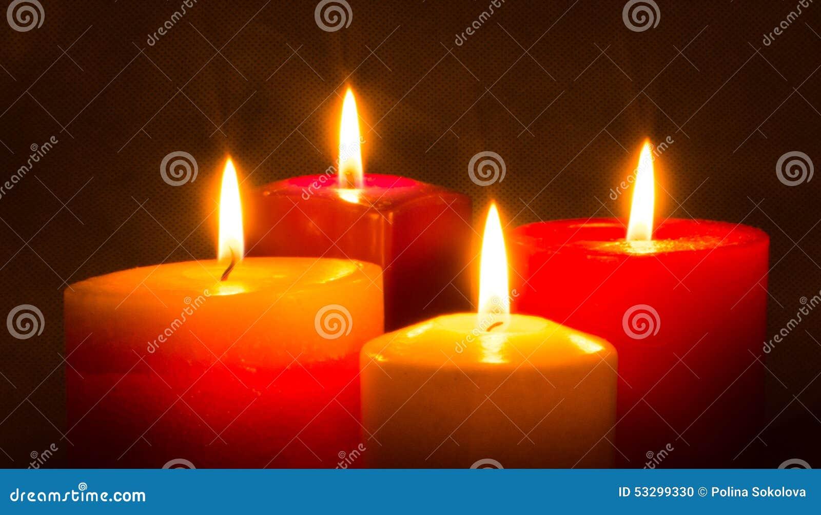 Quattro candele colorate che bruciano nello scuro for Candele colorate