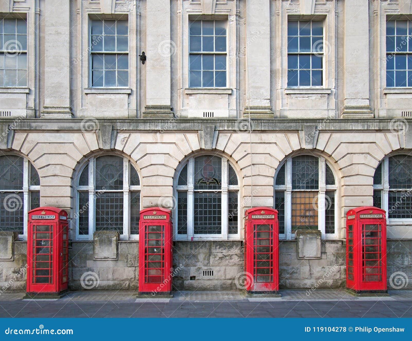Quattro contenitori rossi britannici tradizionali di telefono fuori di vecchia costruzione dell ufficio postale a Blackpool Inghi