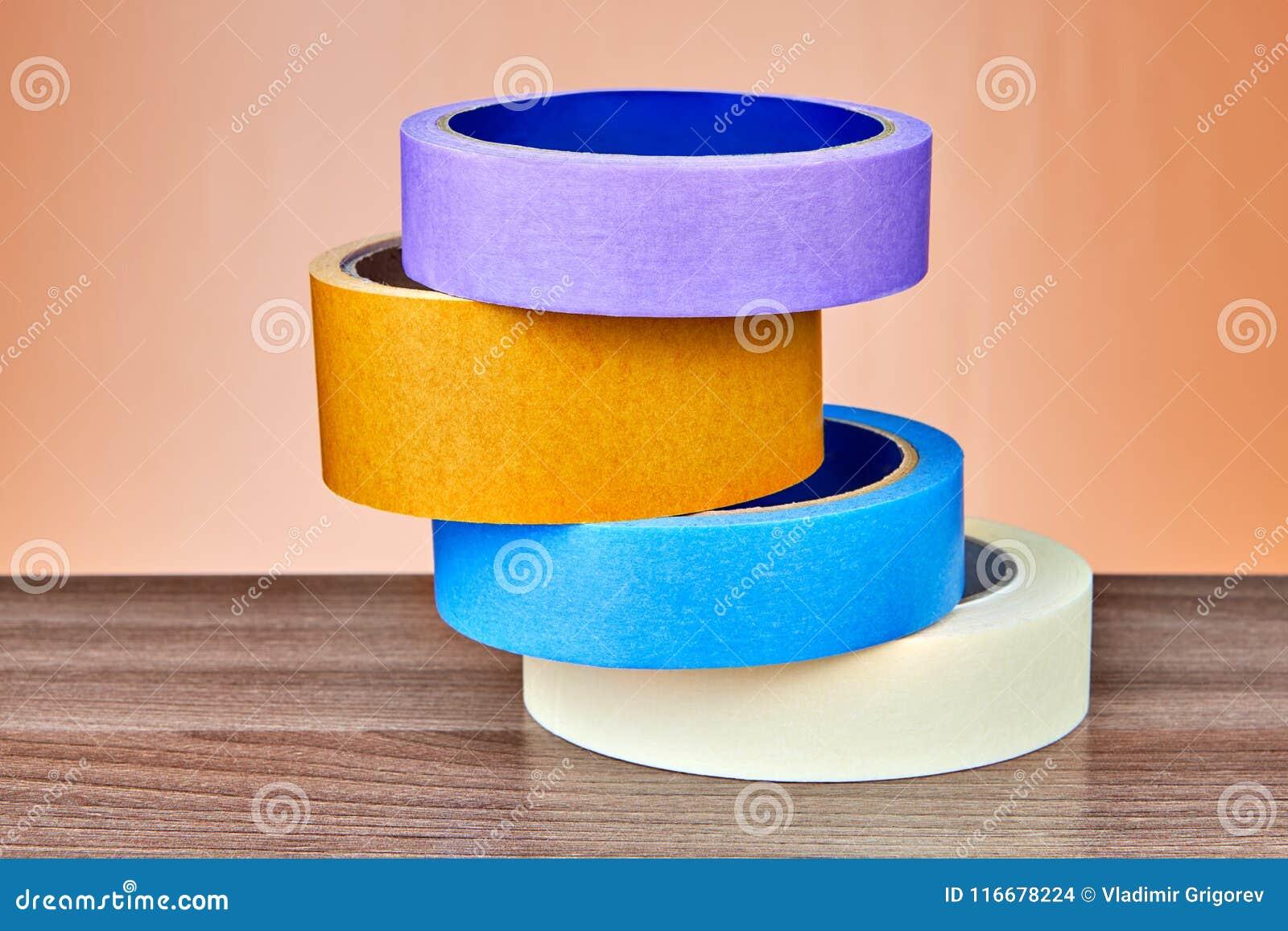 Quattro di rotoli colorati multi del nastro scozzese hanno piegato la pila sulla tavola