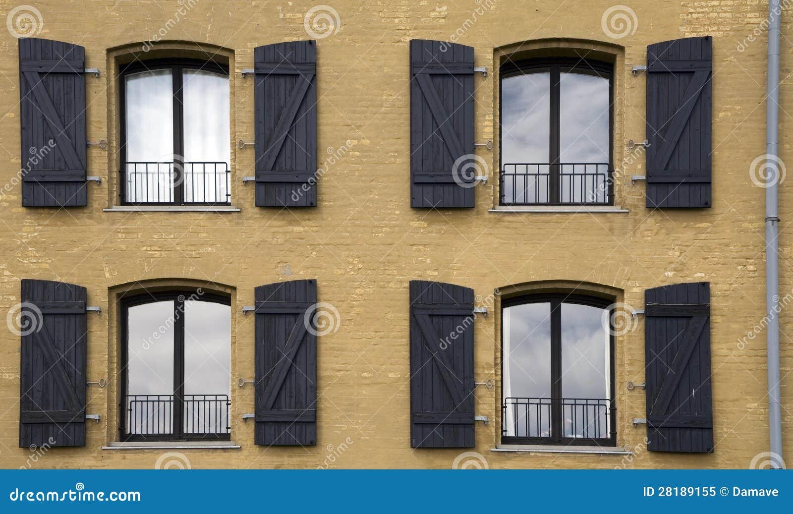 Quattro finestre sulla facciata di una casa immagine stock for Una casa con cornice libera
