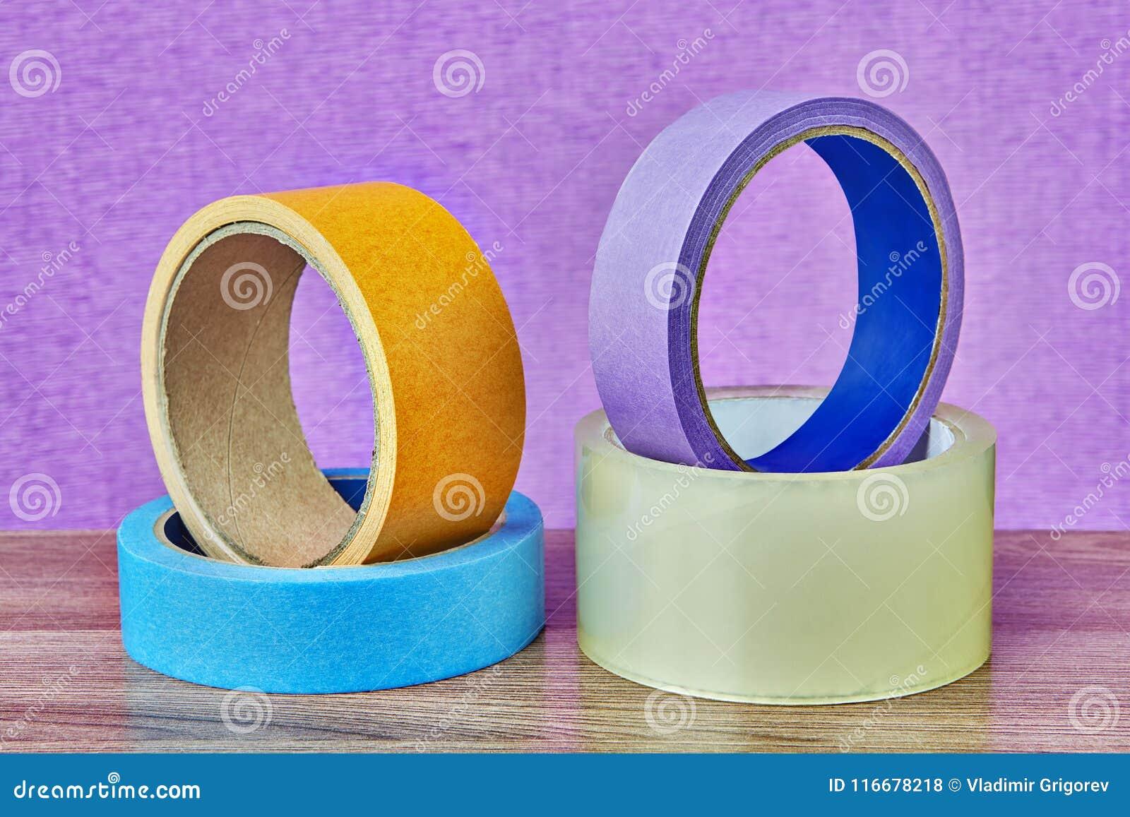 Quattro rotoli del nastro adesivo che si trovano sulla tavola, fondo lilla