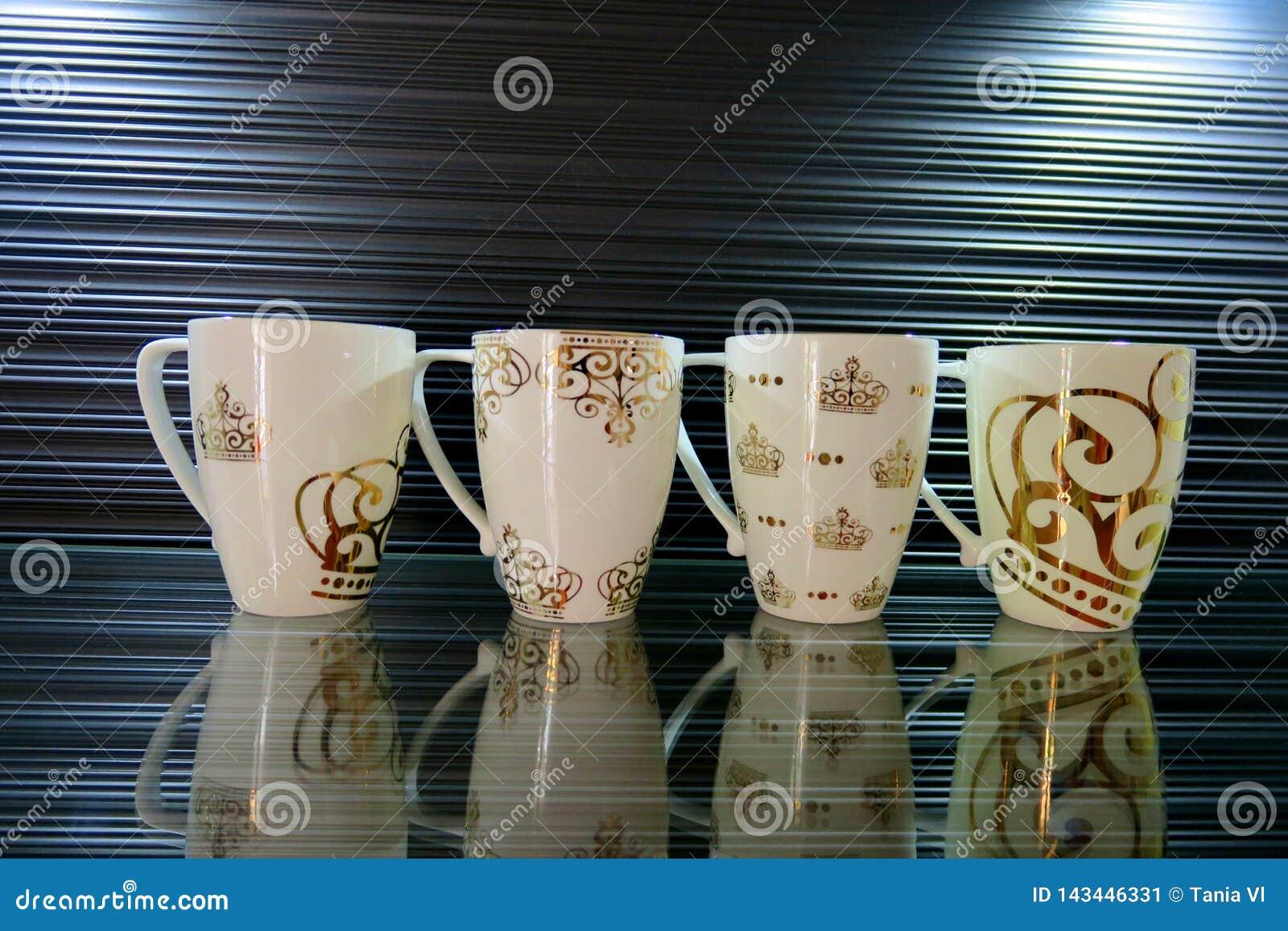 Quattro tazze bianche con differenti modelli su un bello fondo