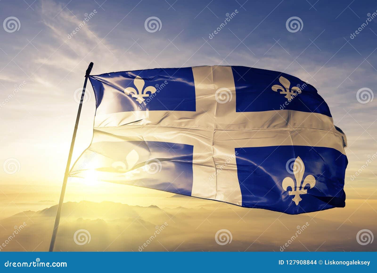 Quebec province of Canada flag textile cloth fabric waving on the top sunrise mist fog