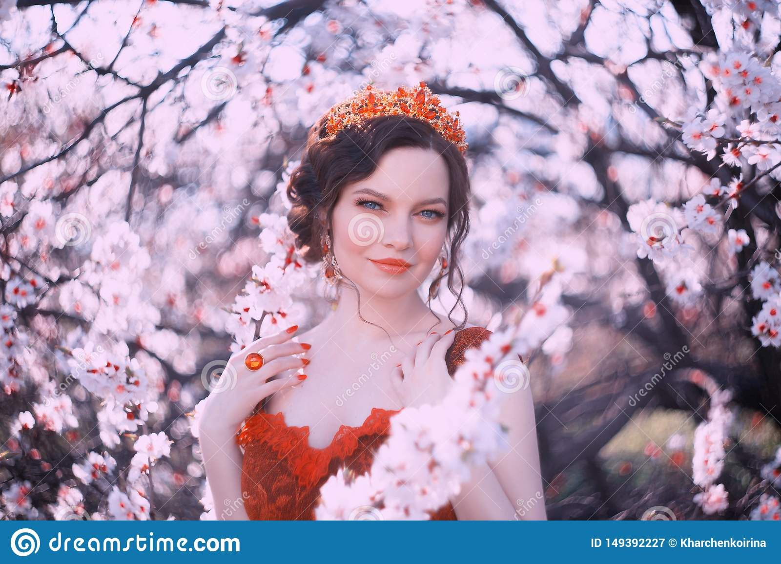 Queen of Spring walks in the blooming garden, a portrait photo of a pretty woman with dark hair and a golden crown on