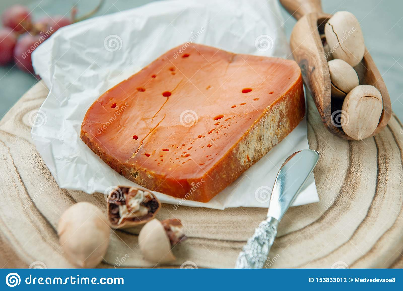 Queijos picantes das guloseimas O queijo Cheddar vermelho, em um fundo de madeira textured bonito com porcas de noz-pecã é um pet