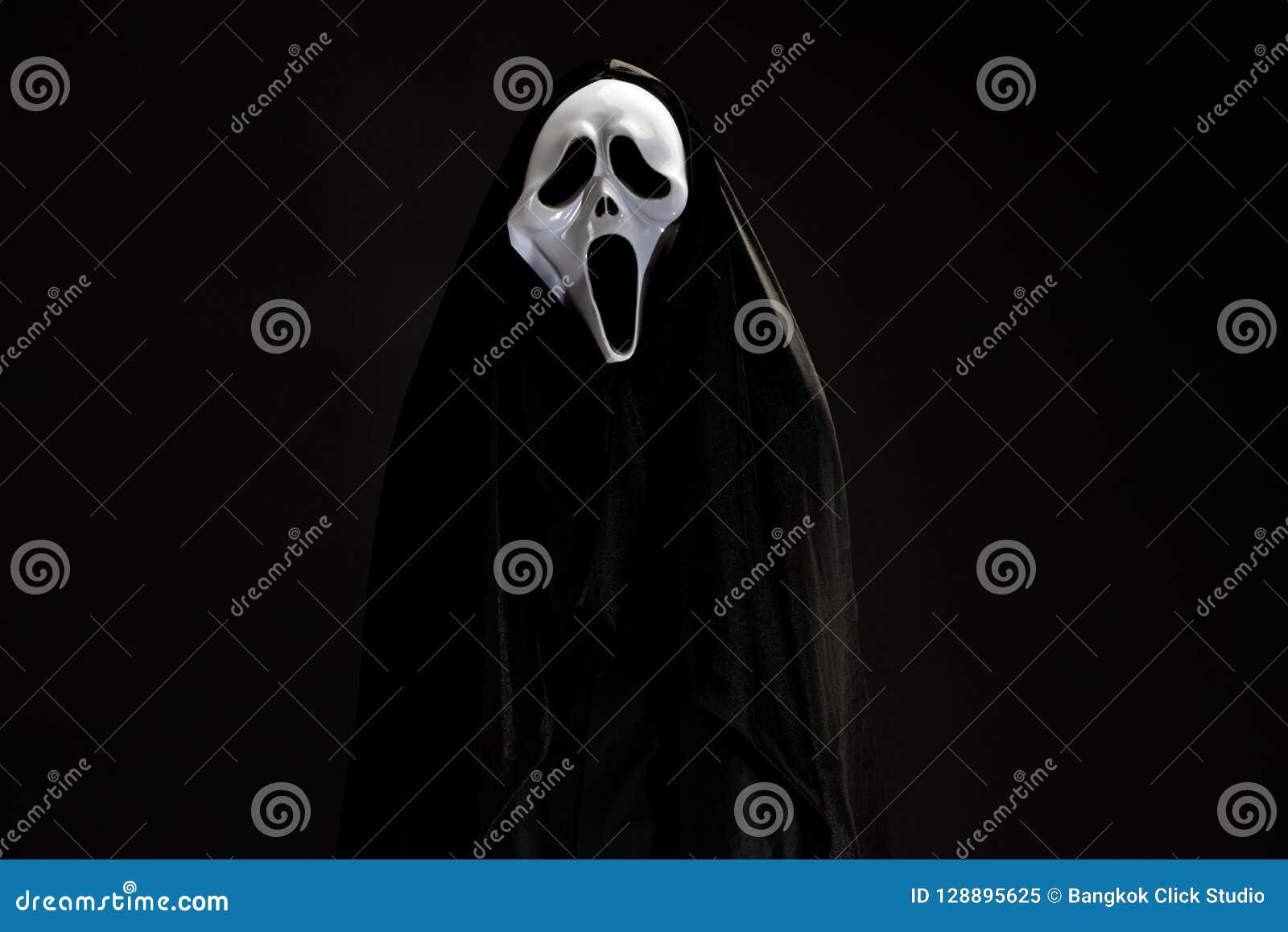 Quelqu un dans la couverture noire avec le masque blanc de fantôme cosplay au C.A. de diable