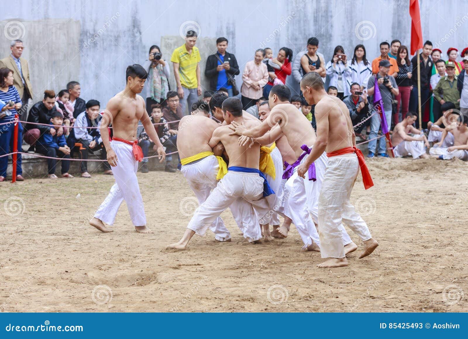 Quelques jeunes hommes jouent avec la boule en bois pendant année lunaire de festival la nouvelle à Hanoï, Vietnam le 27 janvier