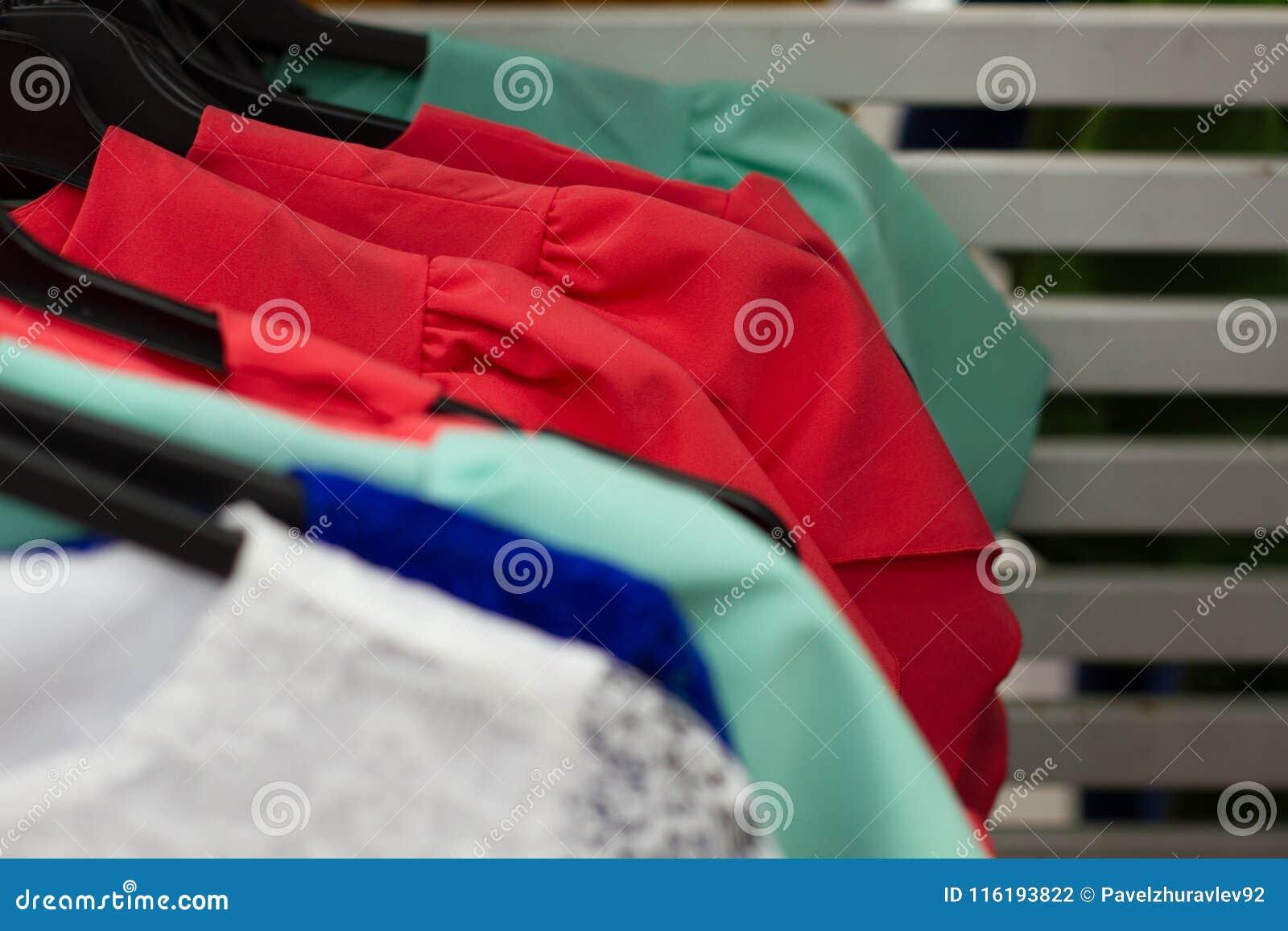 Quelques vêtements utilisés accrochant sur un support sur un marché aux puces Fond de robe Foyer sélectif