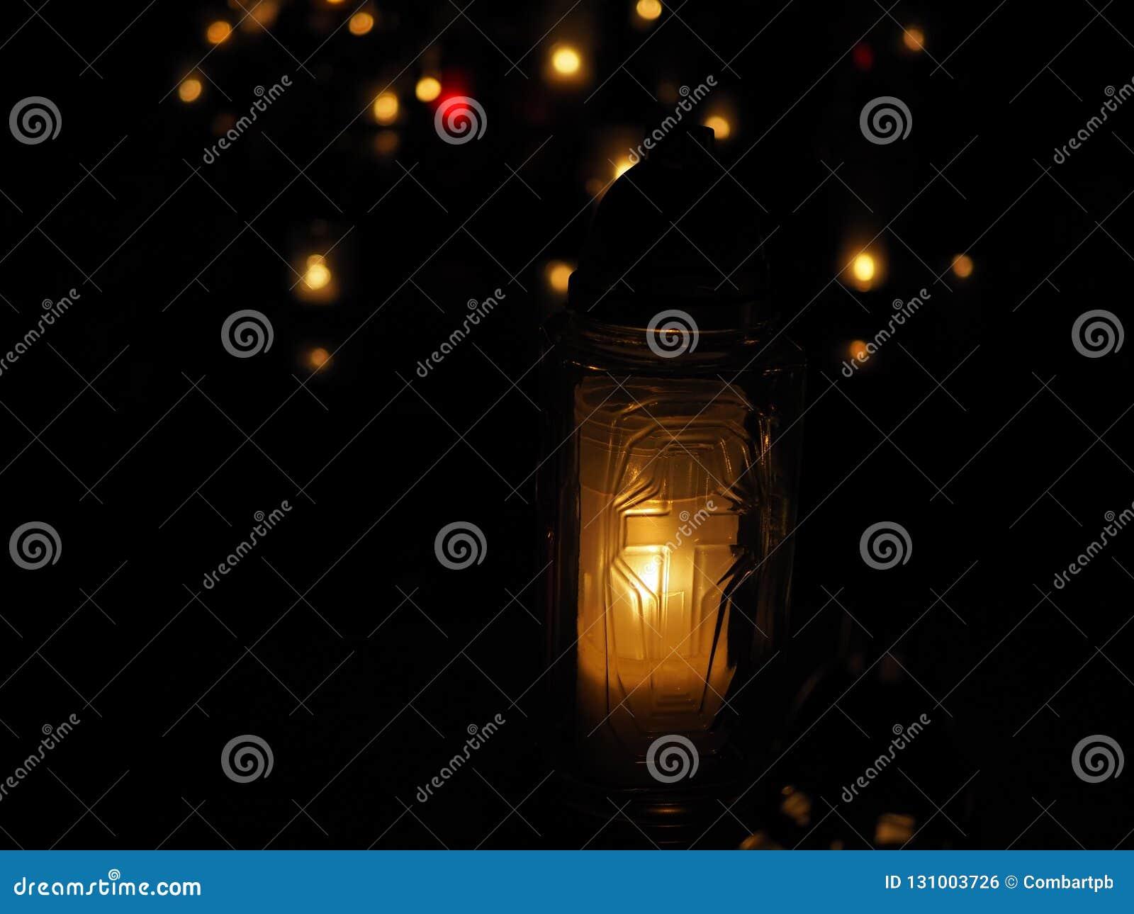 Quema de las velas blancas y coloridas en un cementerio en la noche de todos los santos, luces anaranjadas