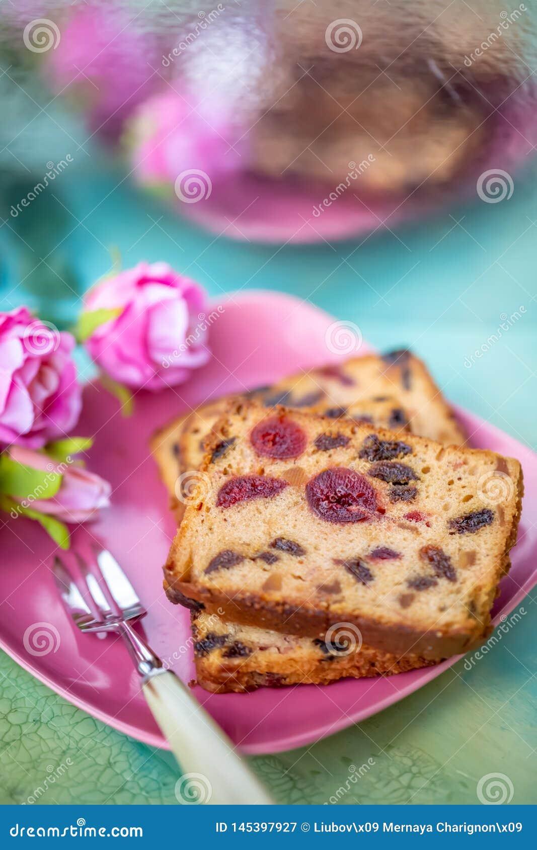 Queque de frutas o magdalena en una placa rosada