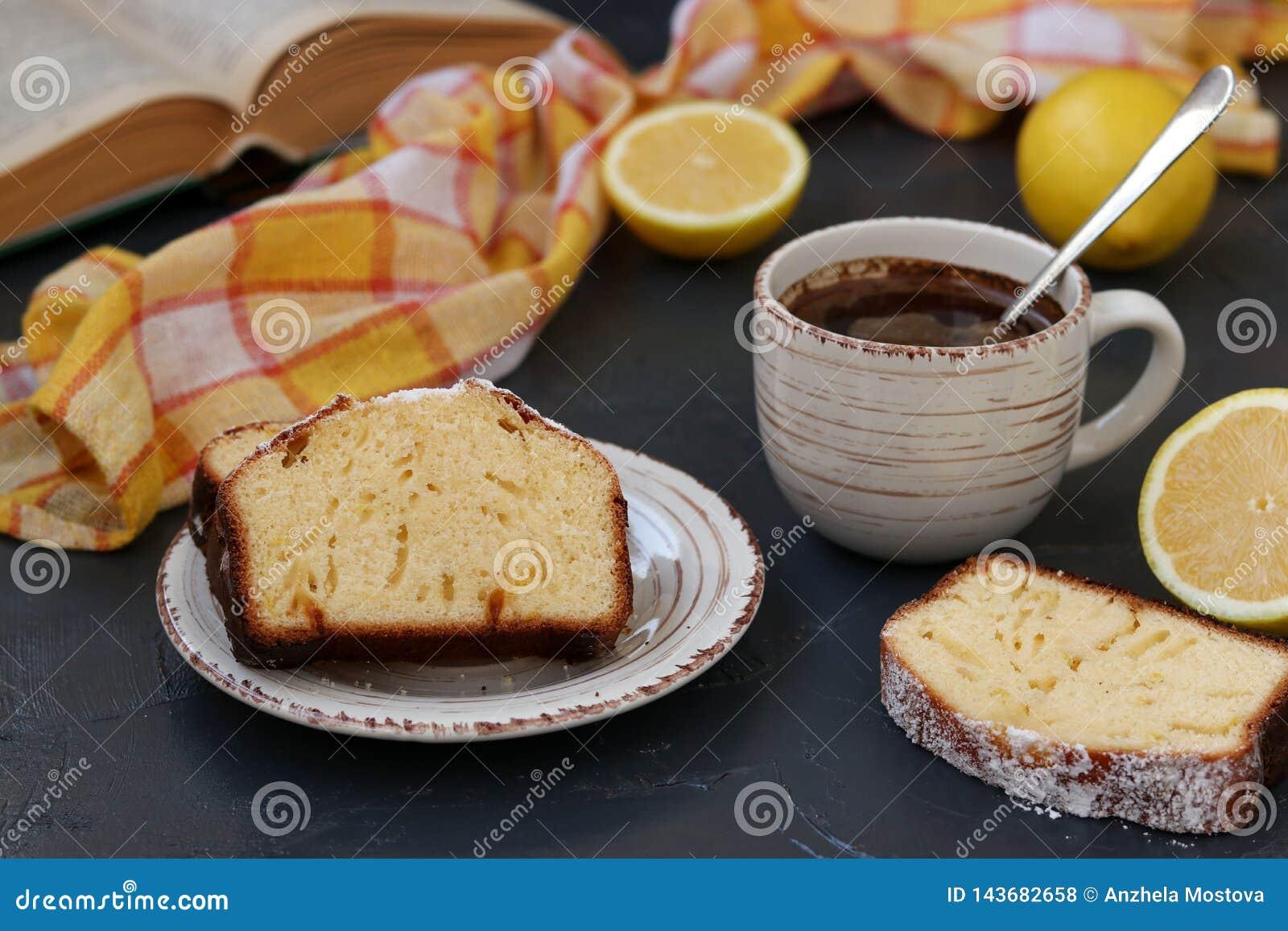 Queque do limão arranjado em uma placa contra um fundo escuro com uma xícara de café no fundo