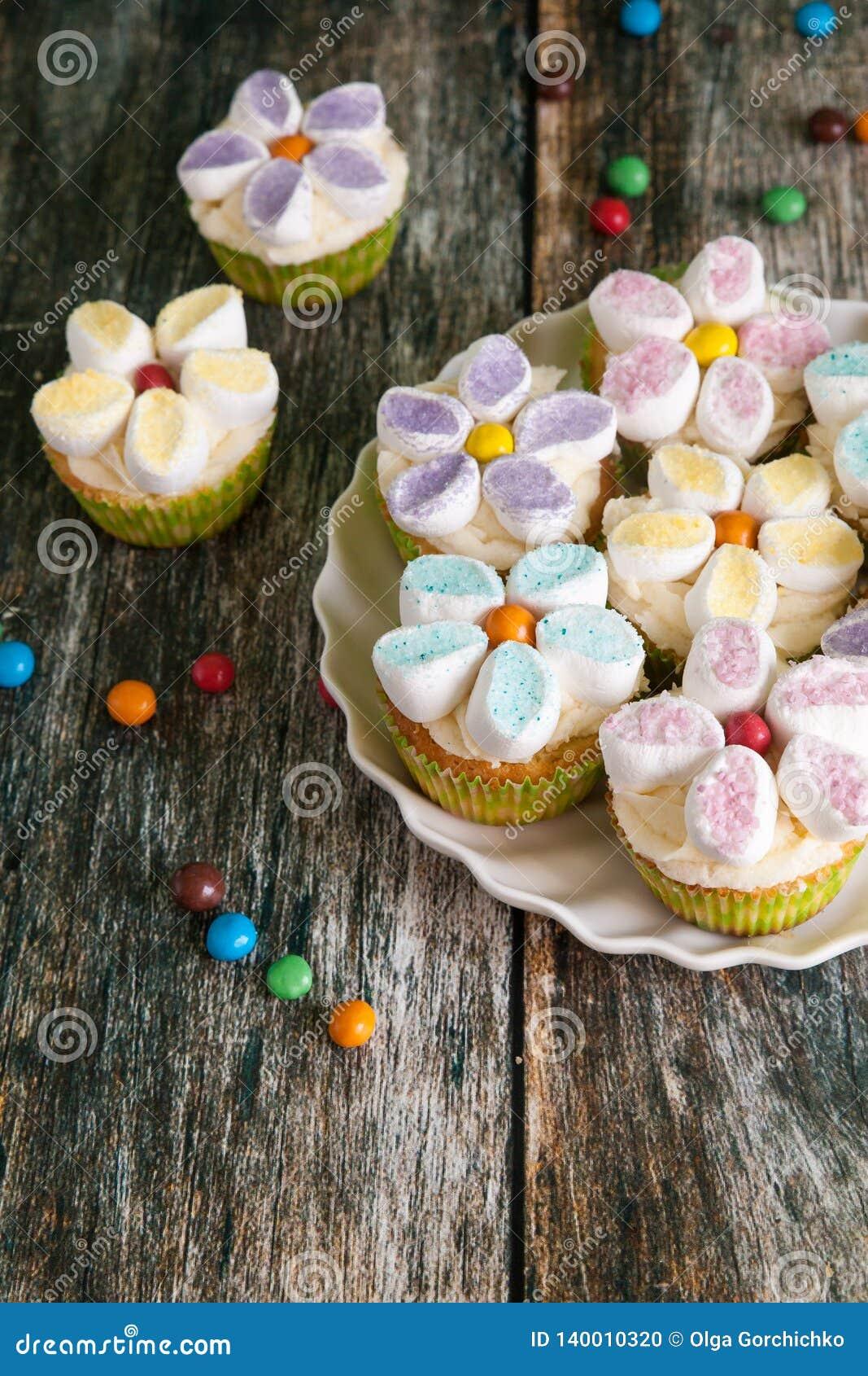 Queques decorados com as flores do creme e do marshmallow da manteiga