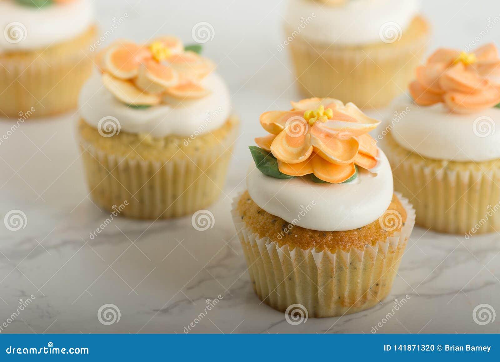 Queques do limão com as flores de Buttercream na tabela de mármore