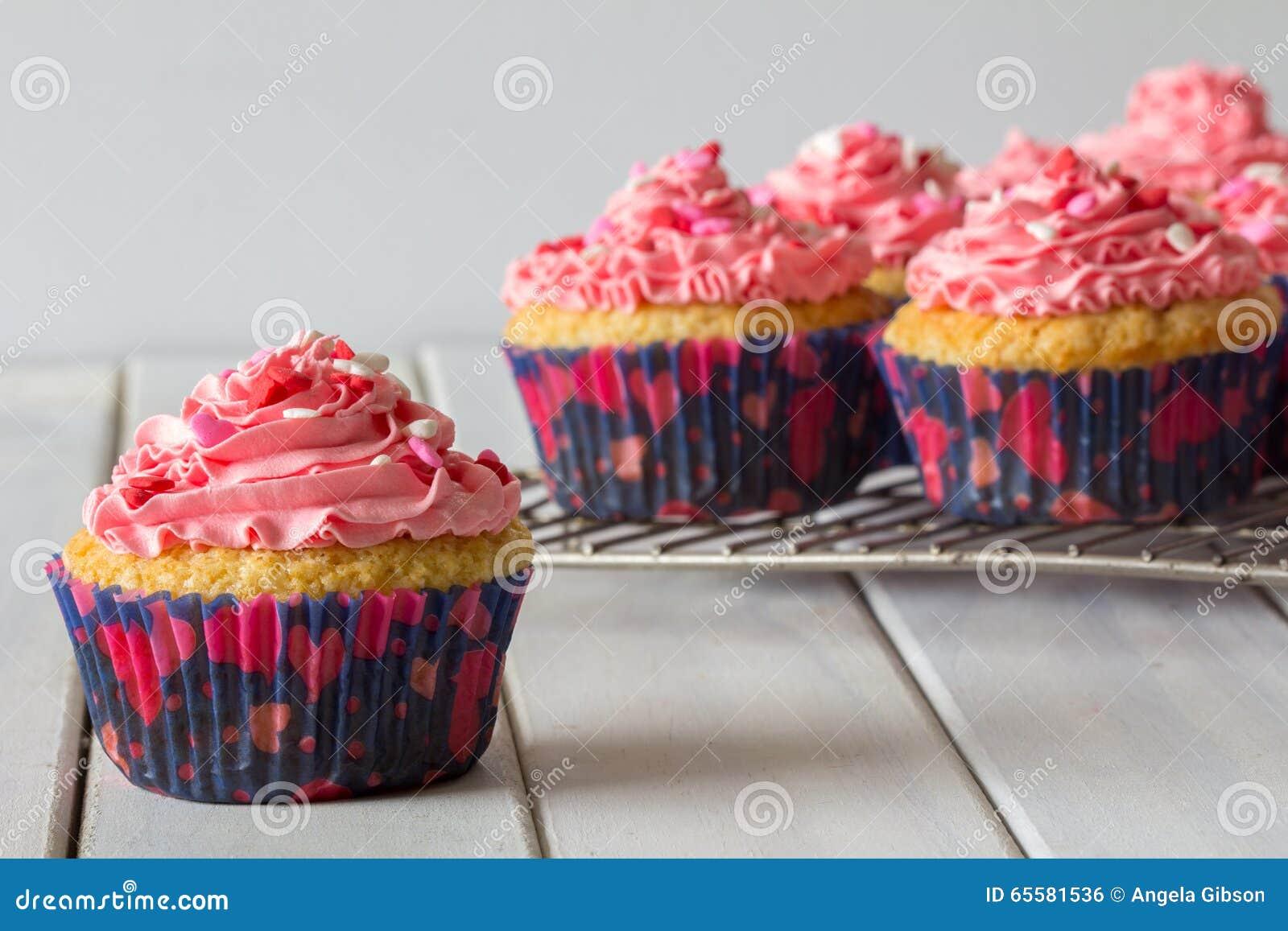 Queques e geada cor-de-rosa na cremalheira do cozimento com um fim acima