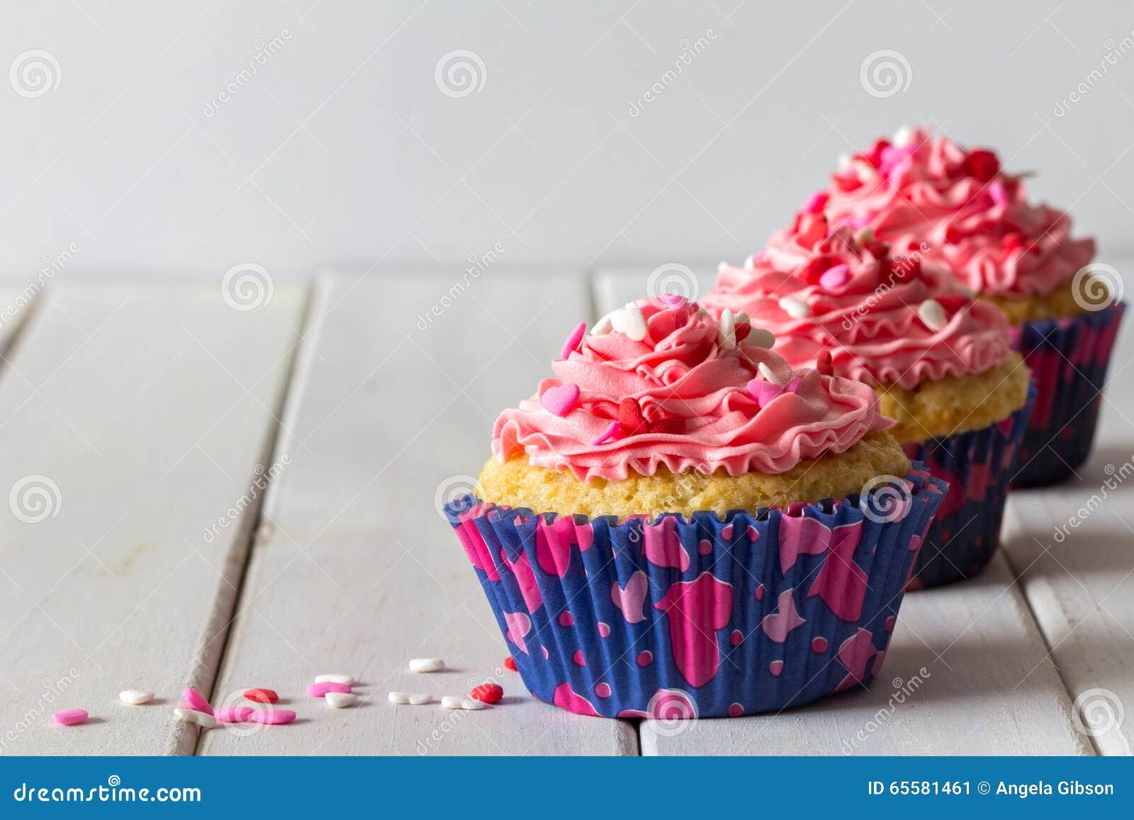 Queques e geada cor-de-rosa na tabela com espaço da cópia