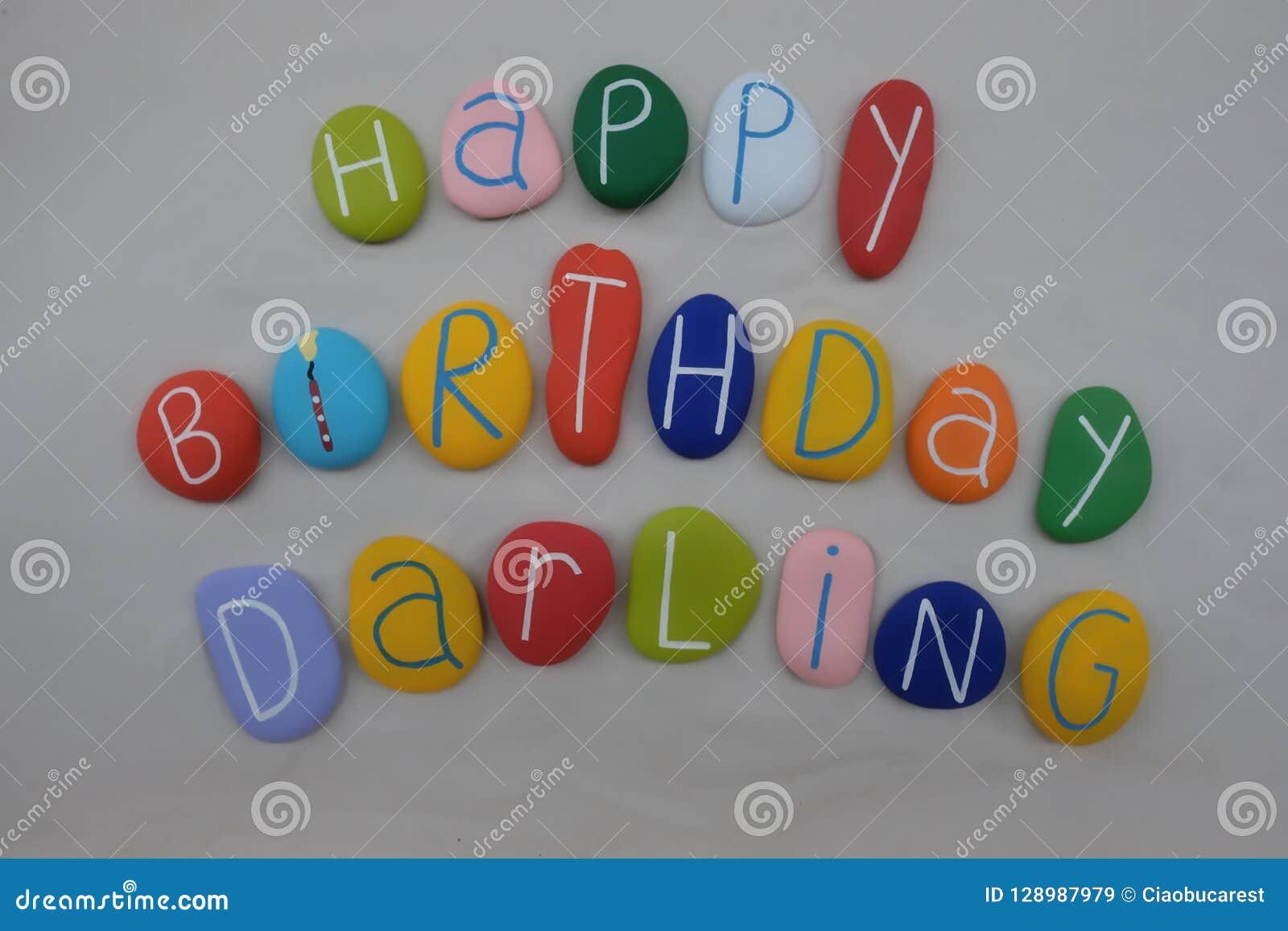 Querido del feliz cumpleaños con las piedras coloreadas sobre la arena blanca