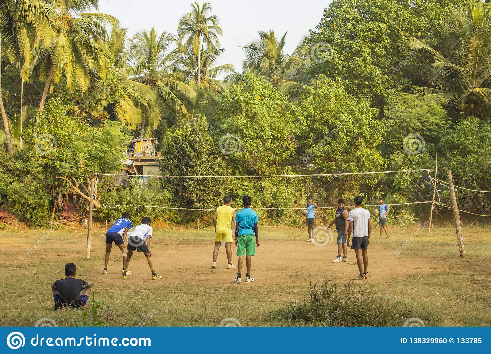 Indian guys playing volleyball outdoors on a green jungle field