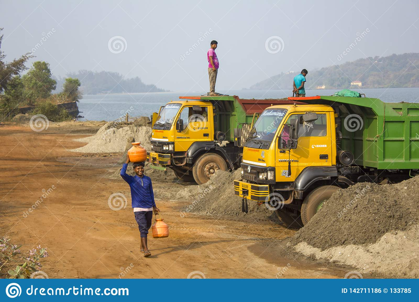 Indian young man carries a barrel of water on his head against the background of yellow trucks