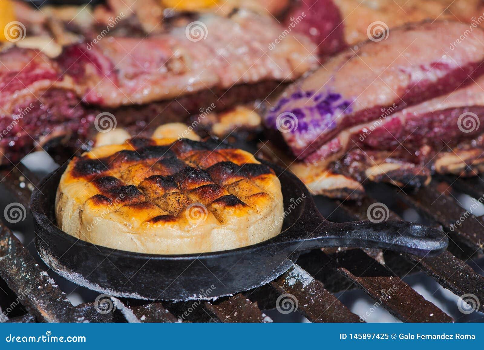 Queso argentino delicioso Provoleta del hilado del provolone que se cocina en una sartén del arrabio sobre la parrilla de una bar
