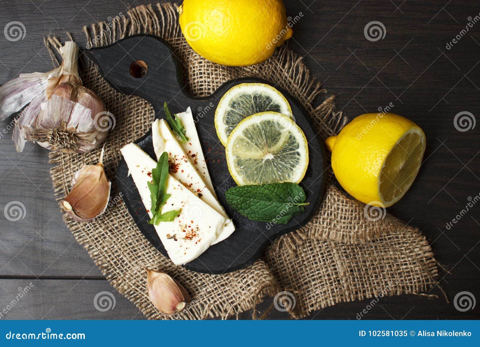 Queso blanco suave con las especias y los limones en un fondo oscuro Estilo rústico