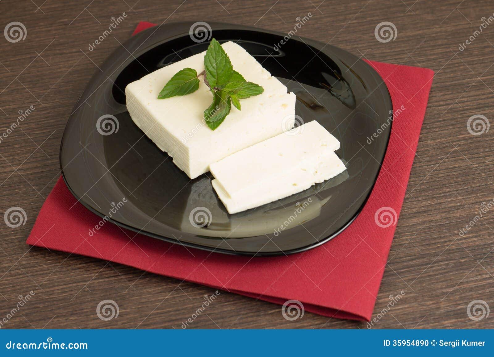 Queso cortado en plato negro con la servilleta