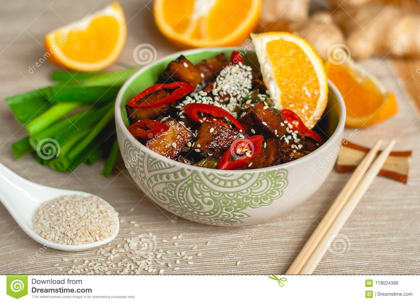 Queso de soja anaranjado sofrito del jengibre con las especias de la cebolla y del chile del sésamo en un cuenco con los palillos