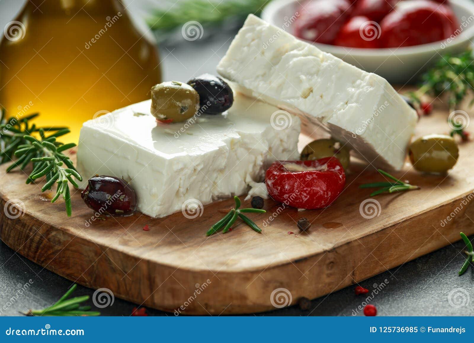 Queso Feta griego del queso con tomillo, romero, aceitunas y paprikas rojos rellenos
