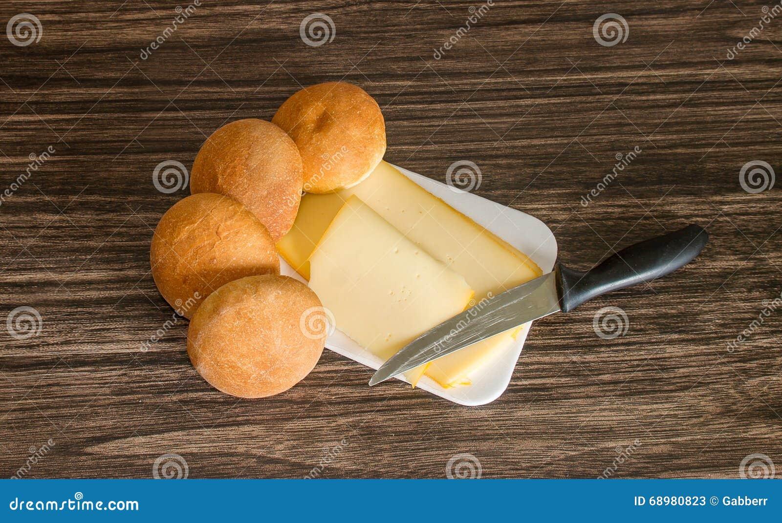 Queso, rollos de pan y cuchillo