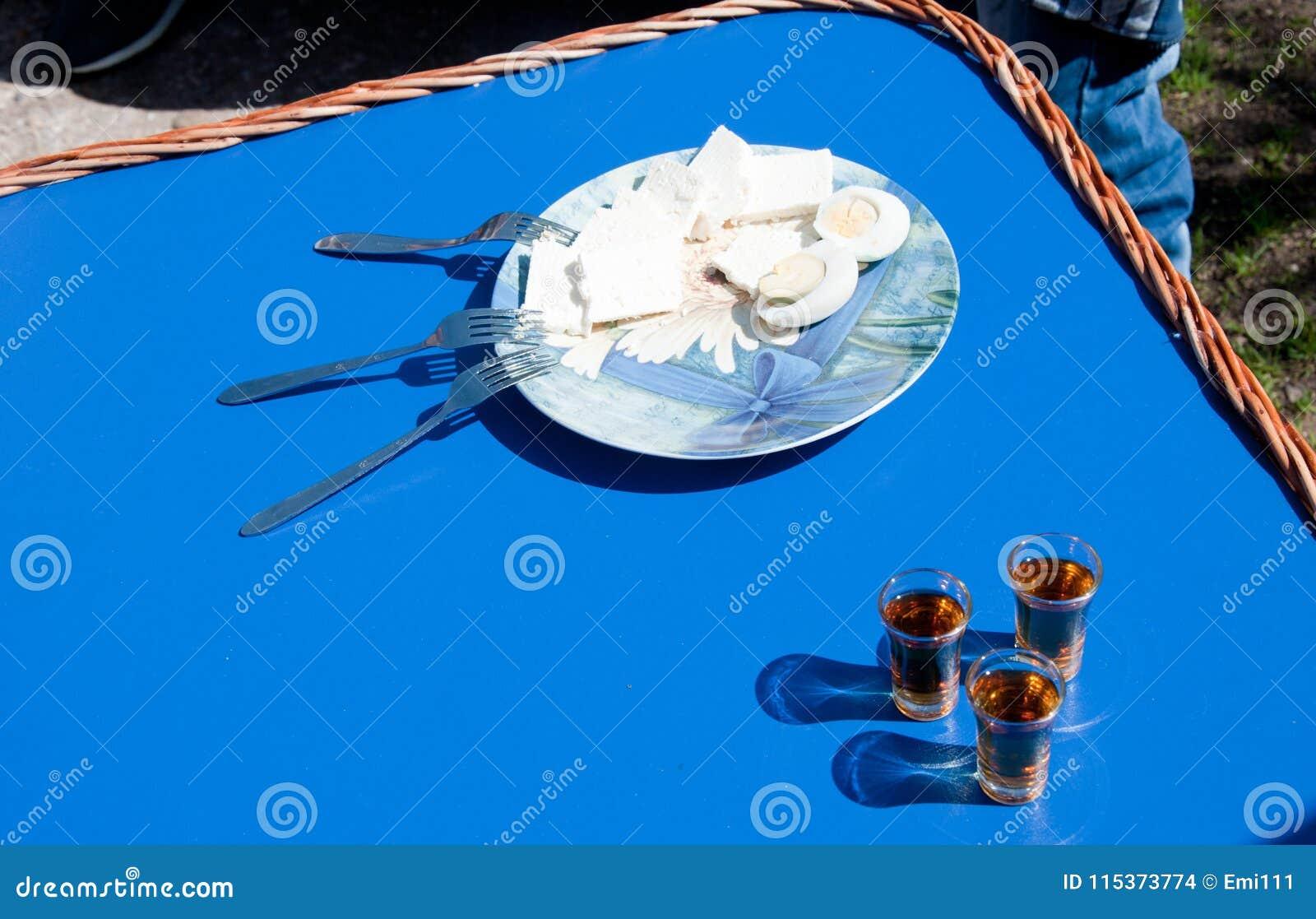 Queso y huevos hervidos en la placa con tres bifurcaciones y tres pequeños vidrios de brandy