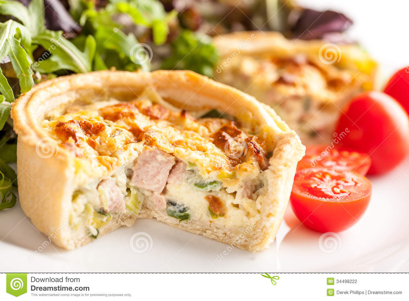 Small Quiche with ham, broccoli and leek on a plate with salad and ...