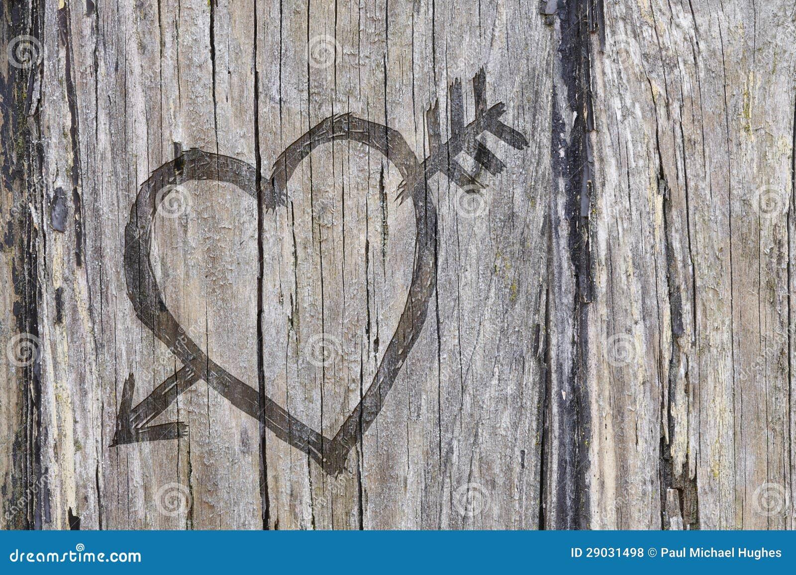 Quiera la pintada del corazón y de la flecha tallada en la madera