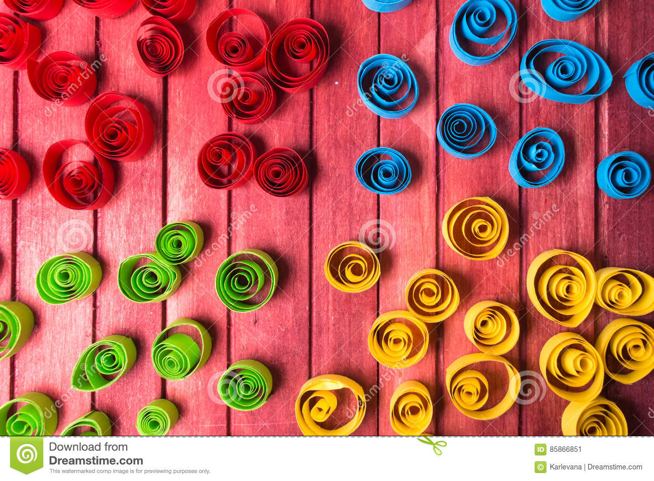 Quilling art. Color paper curls on the wooden table