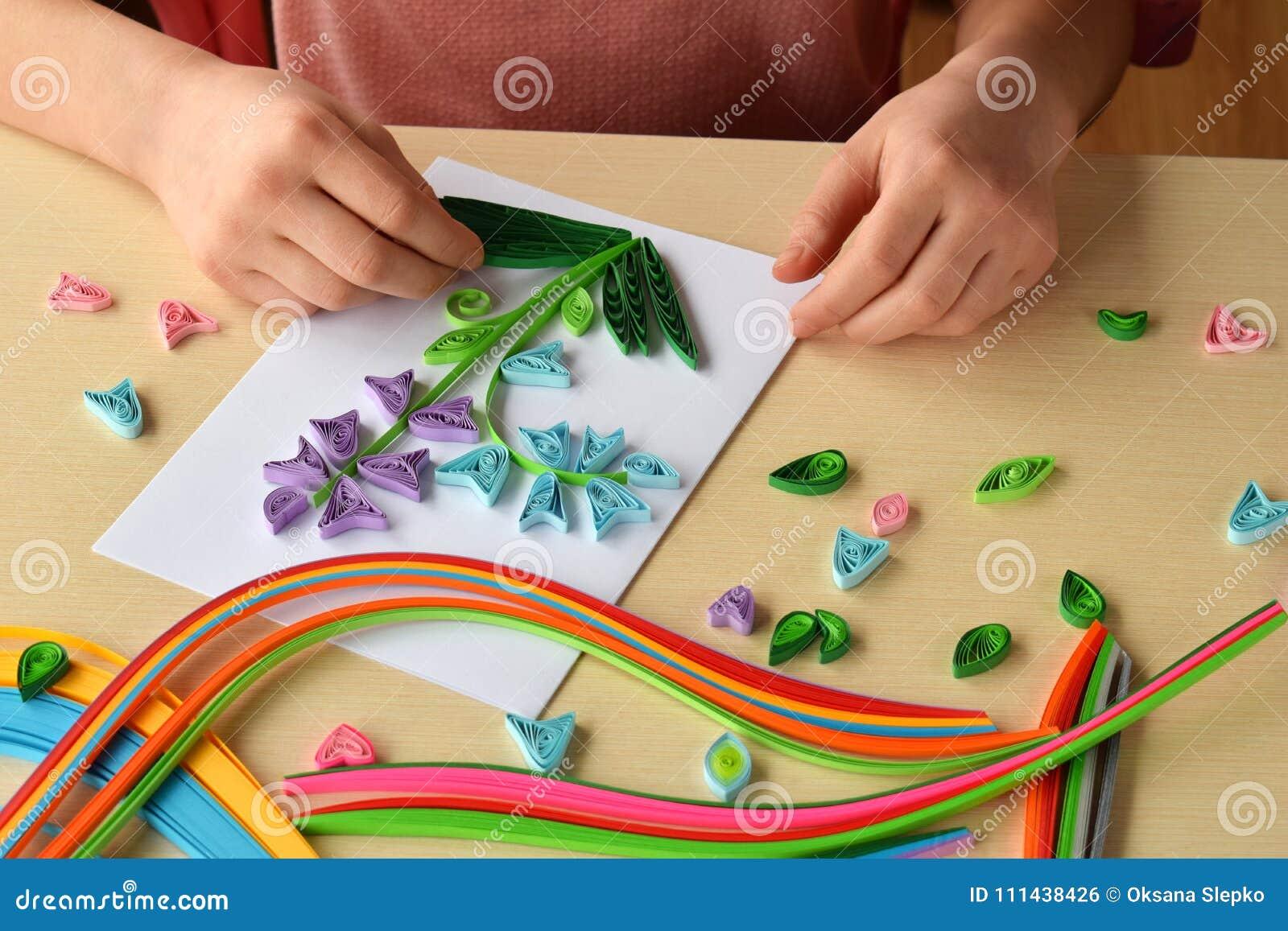 Quilling technika Dziewczyna robi dekoracjom lub kartka z pozdrowieniami Papierowi paski, kwiat, nożyce Handmade rzemiosła na wak