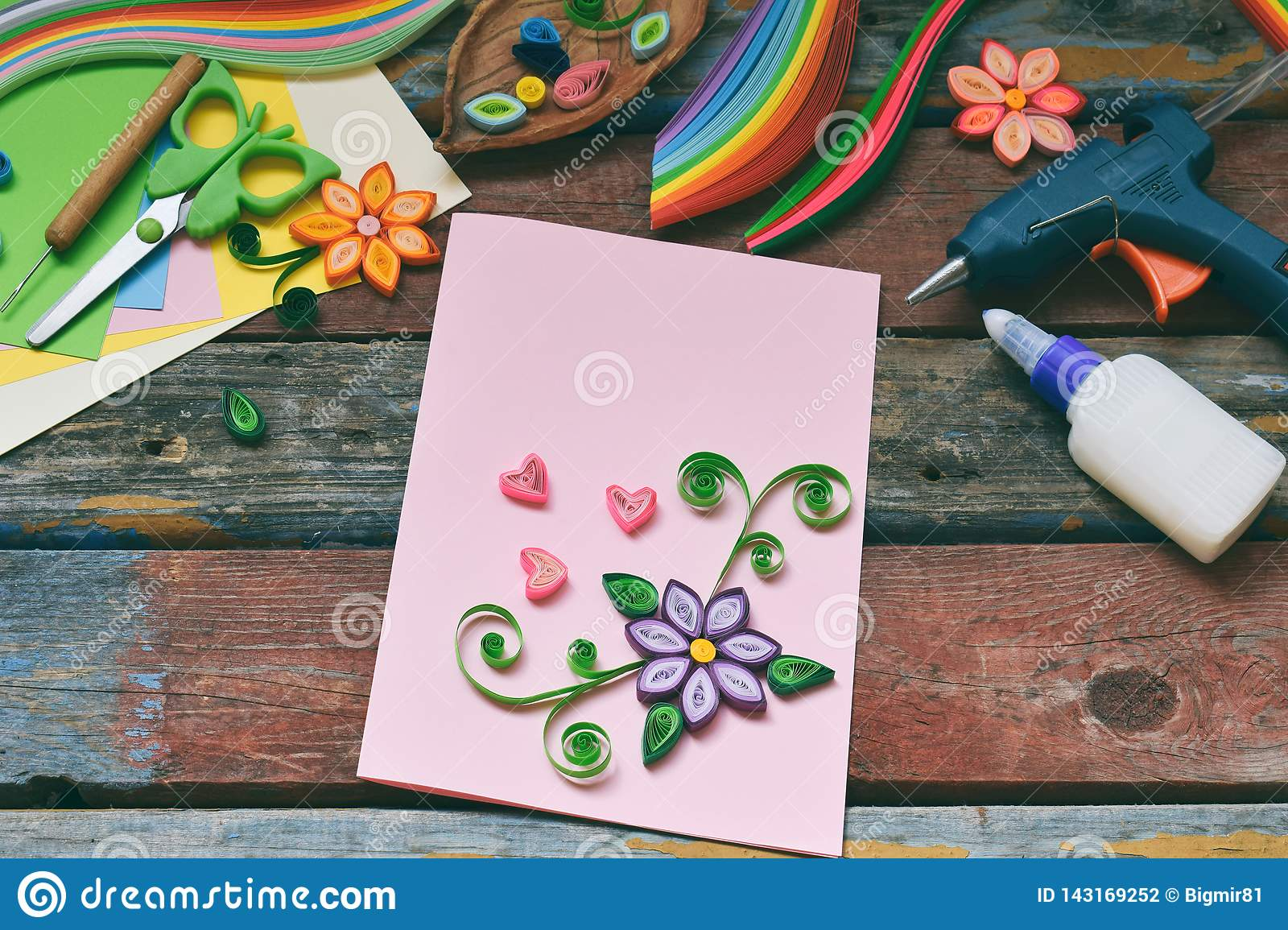 Quilling technique. Paper strips, flowers, scissors, elements. Handmade crafts on holiday theme: Birthday, Mother`s Day, March 8,
