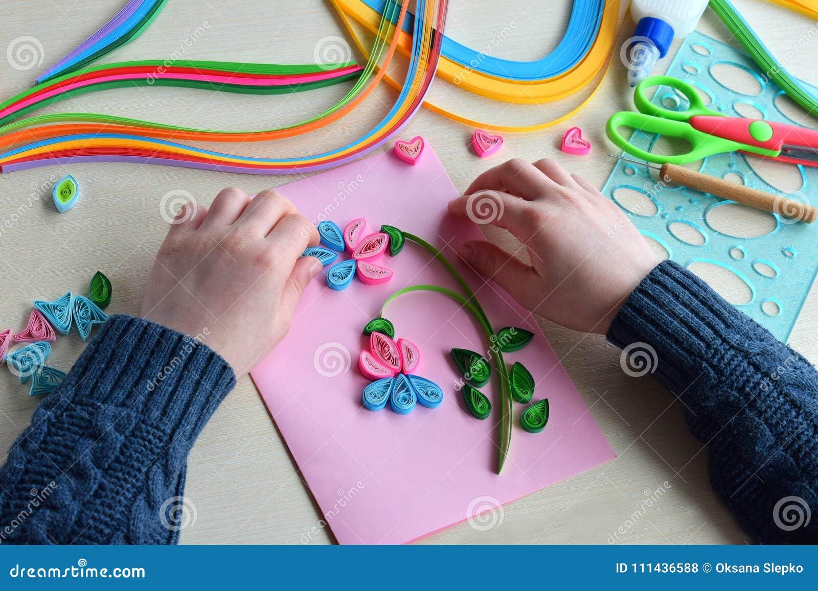 Quillingstechniek Jongen die decoratie of groetkaart maken Document stroken, bloem, schaar Met de hand gemaakte ambachten op vaka
